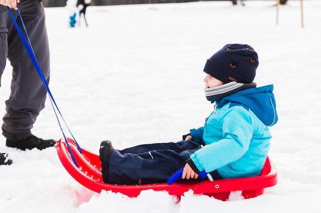 Um menino com trenó vermelho na neve