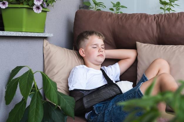 Um menino com um braço quebrado engessado está descansando na varanda de casa