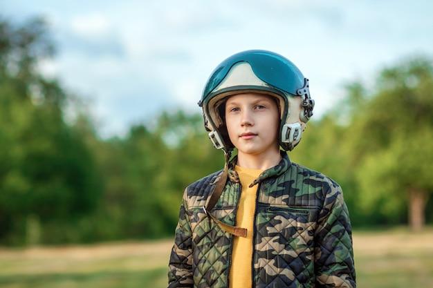 Um menino com um capacete de piloto em um fundo de vegetação. conceito de sonho, escolha da profissão, jogo. copie o espaço.