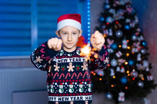 Um menino com um chapéu de papai noel com estrelinhas nas mãos no fundo de uma árvore de natal com luz neon