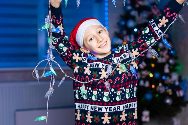 Um menino com um chapéu de papai noel com guirlandas nas mãos no fundo de uma árvore de natal com iluminação neon