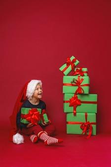 Um menino com um chapéu de papai noel está sentado ao lado de caixas de presente