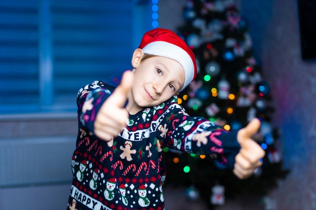 Um menino com um chapéu de papai noel no fundo de uma árvore de natal com iluminação de néon