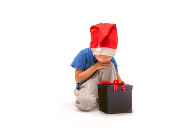 Um menino com um chapéu de papai noel sentado ao lado de uma caixa de presente amarrada com uma fita vermelha
