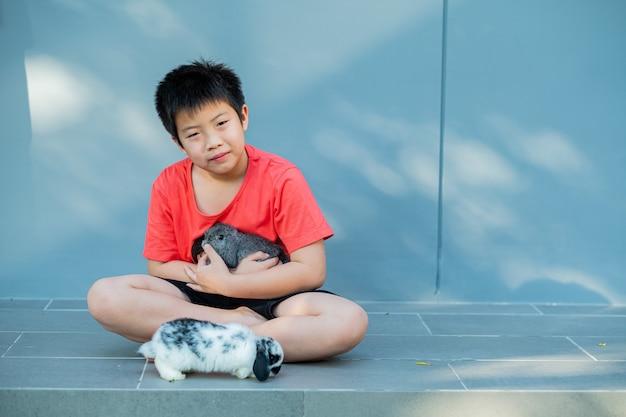 Um menino com um coelho, coelhinho de estimação