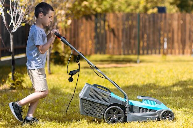 Um menino com um cortador de grama elétrico cortando a grama. menino de beleza podando e ajardinando um jardim