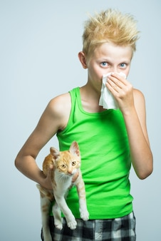 Um menino com um gato vermelho, alergia