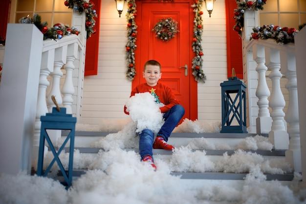 Um menino com um moletom de natal sentado na escada de uma casa