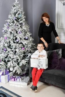 Um menino com um presente para sua mãe ao redor da árvore de natal