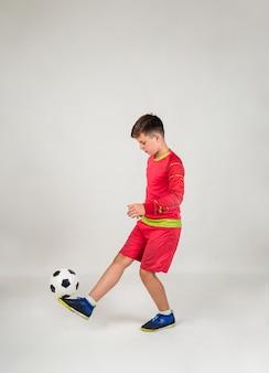 Um menino com um uniforme vermelho de futebol joga uma bola em um fundo branco com um lugar para texto