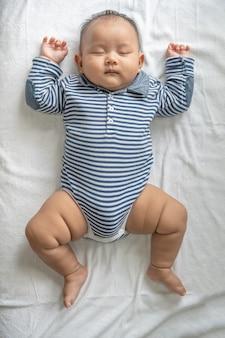 Um menino com uma camisa listrada está dormindo na cama.