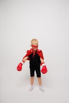 Um menino com uma fantasia de super-herói e luvas de boxe brancas