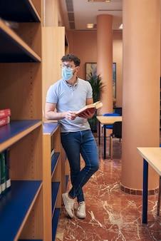 Um menino com uma máscara está em uma biblioteca olhando pela janela