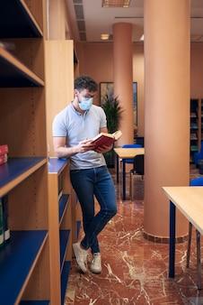 Um menino com uma máscara está olhando um livro na biblioteca