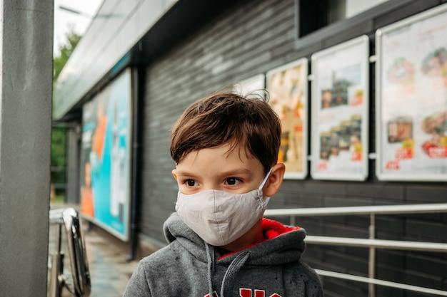 Um menino com uma máscara protetora entra no supermercado