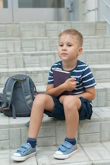 Um menino com uma mochila está parado na escada em frente à escola