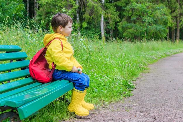 Um menino com uma mochila está sentado em um banco.
