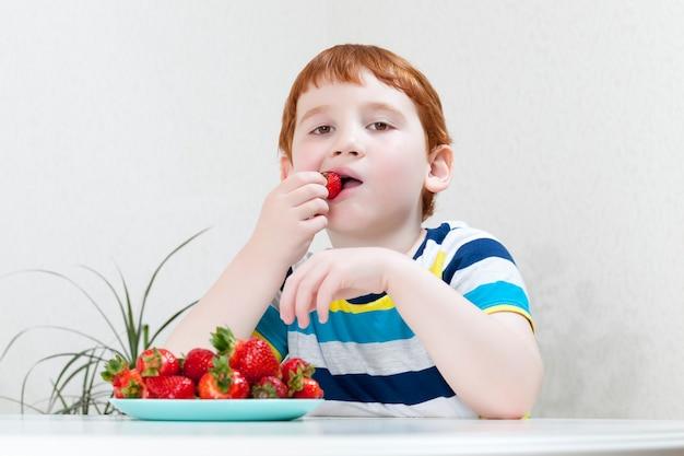 Um menino come morangos maduros