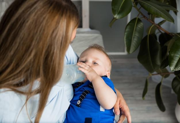 Um menino come uma mamadeira de leite nos braços da mãe