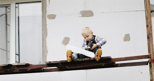 Um menino construtor se senta no andaime com um alicate e uma broca ou chave de fenda