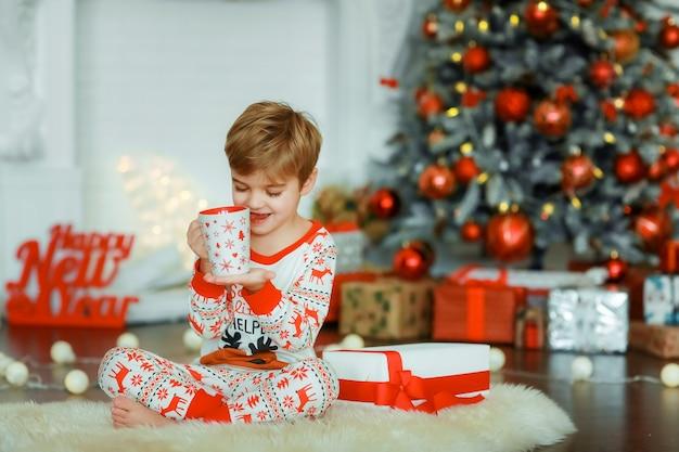 Um menino criança com uma caneca vermelha nas mãos se senta no fundo de uma árvore de natal decorada