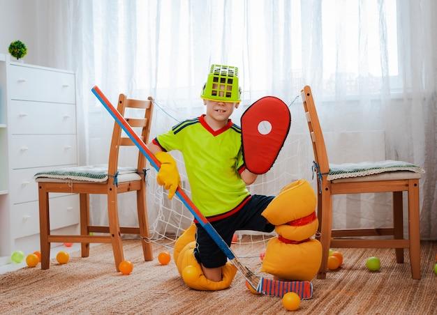 Um menino criança joga hóquei em casa, tendo feito um formulário com as próprias mãos a partir de ferramentas domésticas improvisadas e um portão feito de cadeiras.