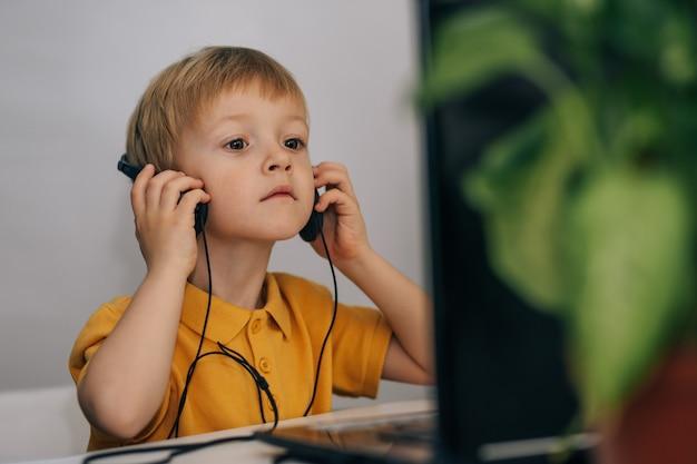 Um menino curioso em idade de escola primária pensa sobre a pergunta dos professores, escolhe a