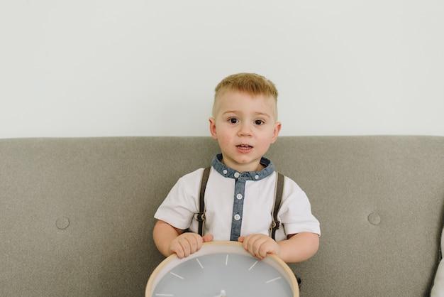 Um menino curioso sentado em um sofá e brincando com um relógio