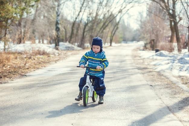 Um menino de 2 anos aprende a andar de bicicleta de equilíbrio na estrada na aldeia