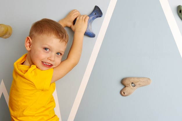 Um menino de 3 a 4 anos sorri para a parede de escalada de uma casa. atividades esportivas infantis