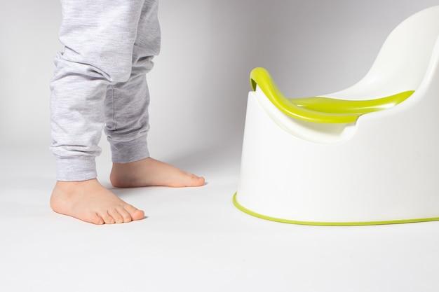 Um menino de 3 anos de calça cinza está parado perto de um pote branco.