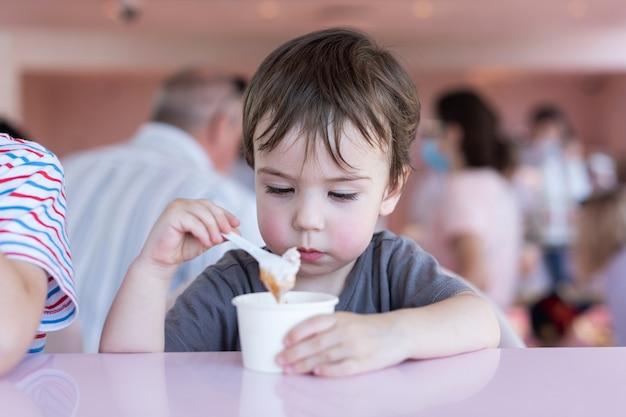 Um menino de 34 anos está tomando sorvete em um café closeup retrato verão no calor da cidade