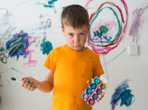 Um menino de 5 anos com um olhar culpado pintado com tinta e pincel na parede do seu quarto.
