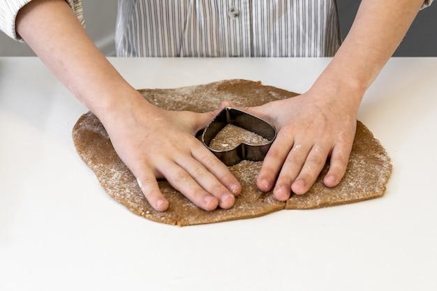Um menino de 7 a 8 anos faz biscoitos com a massa em forma de coração para o feriado