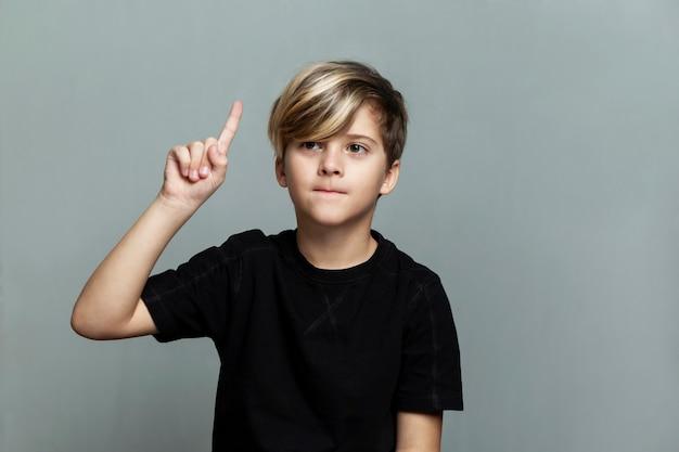 Um menino de 9 anos com um penteado da moda em uma camiseta preta levantou o dedo indicador.