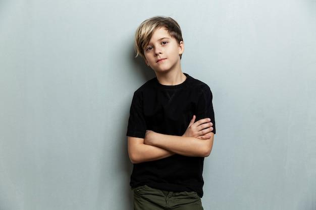 Um menino de 9 anos com uma camiseta preta em pé com os braços cruzados