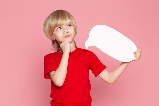 Um menino de cabelos loiros vista frontal em t-shirt vermelha segurando placa branca sobre o backgorund rosa