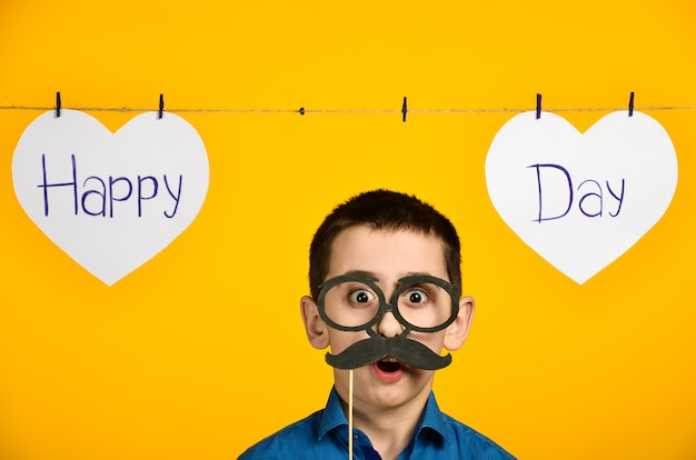 Um menino de camisa azul em um fundo amarelo com um coração e uma inscrição em um dia festivo é torto e veste óculos e bigode