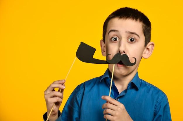 Um menino de camisa azul em um fundo amarelo faz uma careta e veste um bigode e segura um cachimbo