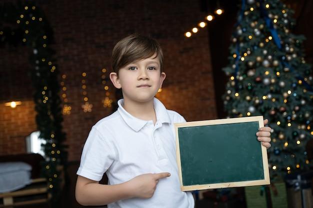 Um menino de camisa branca fica perto da árvore de natal e segura uma placa com um espaço em branco para texto. conceito de férias de natal