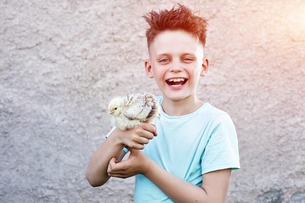 Um menino de camiseta azul com frango fofo rindo no fundo desfocado