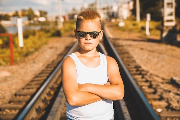 Um menino de camiseta branca e óculos pretos está parado na ferrovia.