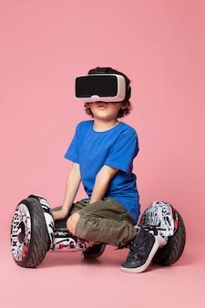 Um menino de criança bonito vista frontal em t-shirt azul jogando vr em segway no espaço rosa