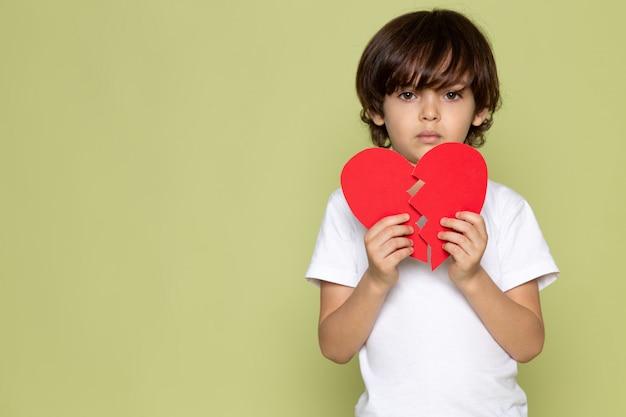 Um menino de criança bonito vista frontal em t-shirt branca e em forma de coração rasgado no espaço colorido de pedra