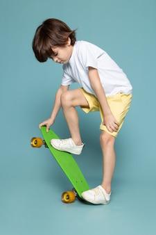 Um menino de criança vista frontal em camiseta branca e calça jeans amarela andando de skate verde no espaço azul