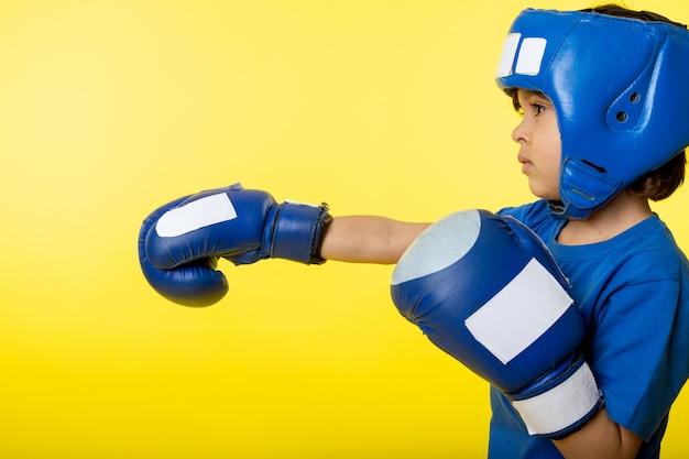 Um menino de criança vista frontal em luvas azuis e capacete azul boxe na parede amarela
