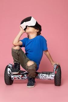 Um menino de criança vista frontal em t-shirt azul jogando vr em segway no espaço rosa