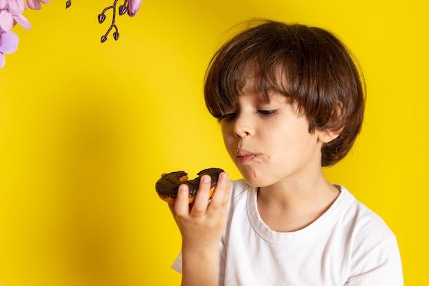 Um menino de criança vista frontal em t-shirt branca comendo rosquinhas no chão amarelo