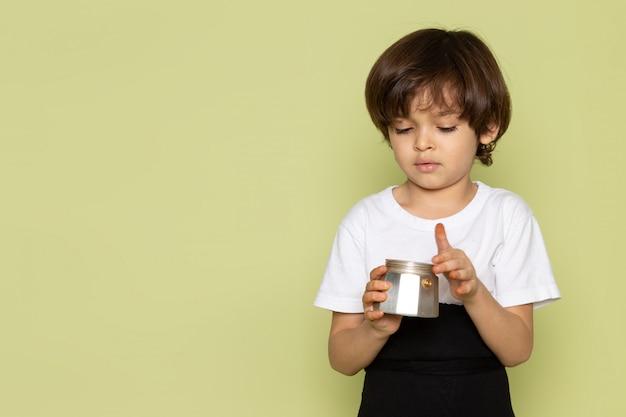 Um menino de criança vista frontal em t-shirt branca segurando café em pó sobre a mesa de pedra colorida