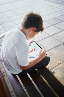 Um menino de escola espanhola desenhando em um tablet sentado no banco do parque